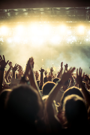 cheer: Audience with hands raised at a music festival and lights streaming down from above the stage. Soft focus, blurred movement. Stock Photo
