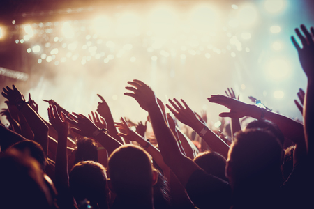live happy: Audience with hands raised at a music festival and lights streaming down from above the stage. Soft focus, blurred movement. Stock Photo