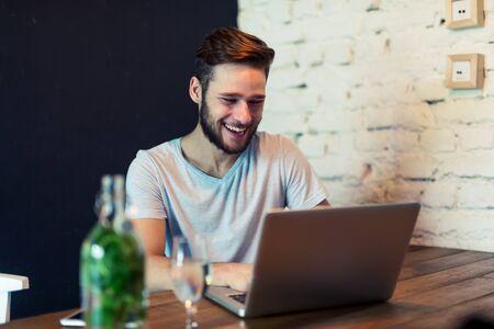 bonhomme blanc: Tir d'un jeune homme travaillant sur un ordinateur portable dans un caf�. mise au point s�lective, la lumi�re naturelle, higer ISO, l'image granuleuse. Banque d'images