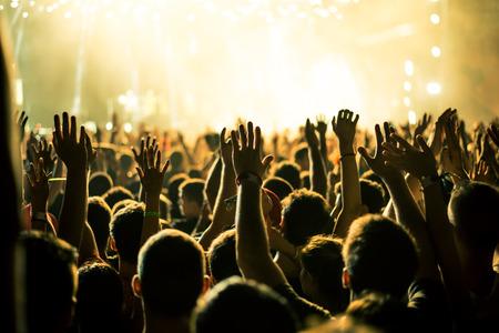 alzando la mano: Audiencia con las manos levantadas en un festival de m�sica y luces de streaming desde arriba del escenario. Enfoque suave, el movimiento borroso. Foto de archivo