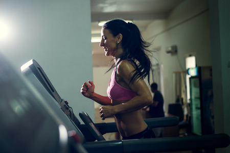 Shot of a girl running on the treadmill at their local gym. Dramatic light, selective focus, toned image.