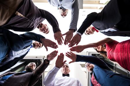 Samen zijn we sterker. Groupe van jongeren gebaart de kracht van saamhorigheid. Lage, brede hoek geschoten, selectieve aandacht op hun handen, smalle diepte van ingediend.