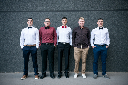 men standing: Group of elegant young business men standing against the wall.
