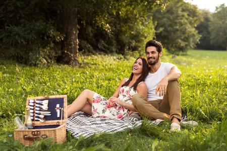 ロマンチックな時間を過ごしていると、夏のピクニックを楽しんで幸せな若いカップルのショット。自然の光、選択的なフォーカス。