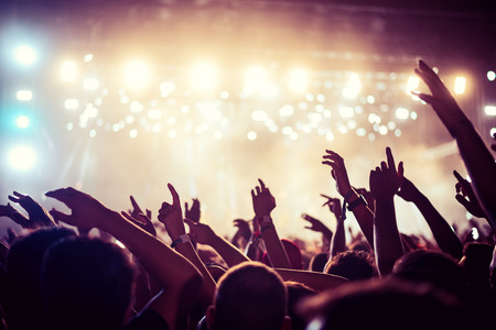 Audience with hands raised at a music festival and lights streaming down from above the stage. Soft focus, high ISO, grainy image. Stockfoto