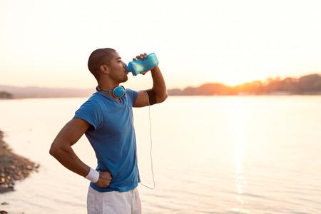 personas tomando agua: Recortar foto de un deportista joven agua potable mientras se ejecuta en orilla del río. Sunset tonos cálidos.