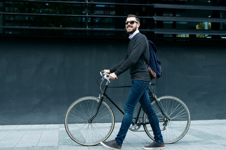 male model: A young smiling stylish businessman pushing a bicycle while going to work.