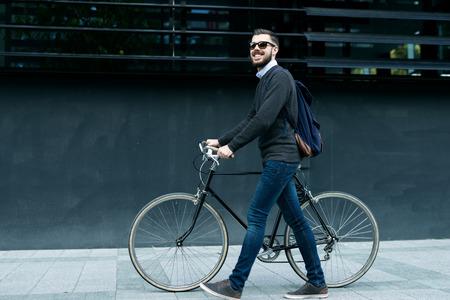 Een lachende jonge stijlvolle zaken man duwen een fiets terwijl het gaan om te werken.