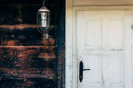 laterns: Shot of an old rustic door and lantern on the wall. Stock Photo