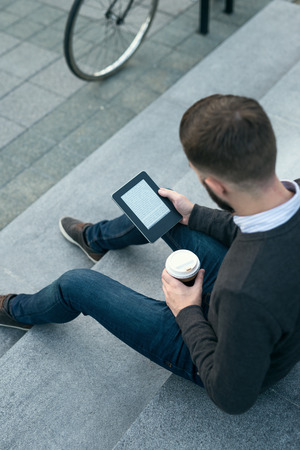 A stylish young man sitting and holding bookreader while drinking coffee.