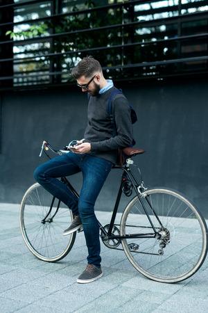 자신의 자전거와 함께 작업을 진행하는 동안 자신의 휴대 전화를 사용하는 사업가의 총입니다. 선택적 포커스, 필드의 좁은 깊이.