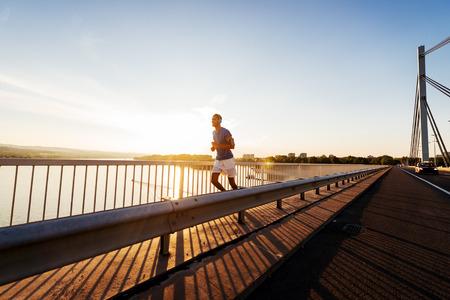 若い男性朝橋の上を実行します。レンズのフレアが、温かみのある色調。 写真素材
