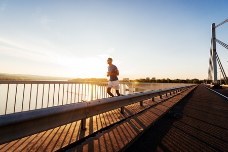 Jonge mannelijke ochtend lopen op de brug. Lens flare, warme tinten.