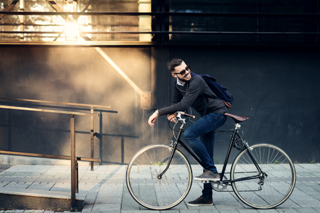 mochila viaje: Un hombre de negocios con estilo joven de ir a trabajar en bicicleta.