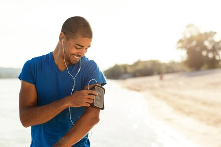 playlist: Shot of an attractive and sporty young man starting his music playlist outdoors. Stock Photo