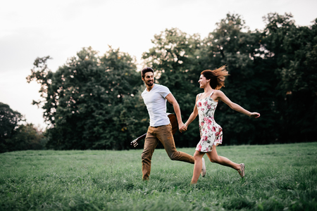 Shot of a young couple holding hands and running through the park. Blurry movement, soft focus.