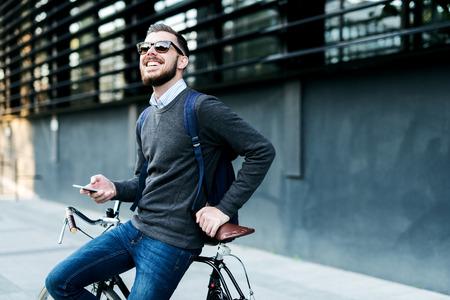 彼は自転車で仕事に行っている間彼の携帯電話を使用して実業家のショット。