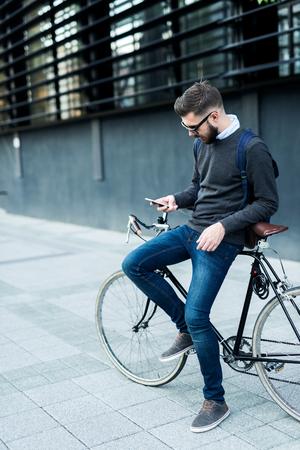 그의 자전거와 함께 작동하도록가는 동안 자신의 휴대 전화를 사용하여 사업가의 총입니다.