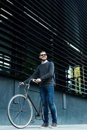 작업을 진행하는 동안 자전거를 밀어 젊은 미소 세련된 사업가.
