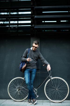 休憩を取って、仕事に行っている間に携帯電話を使用してカジュアルな服を着たビジネスマンのショット。 写真素材