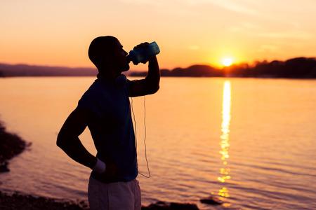 tomando agua: Recortar foto de un joven shulette corredor de pie en la orilla del río en la puesta del sol y el agua potable. Sunset tonos cálidos.