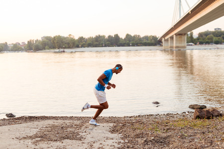 men running: Young male athlete having a morning jogging next to the river. Stock Photo