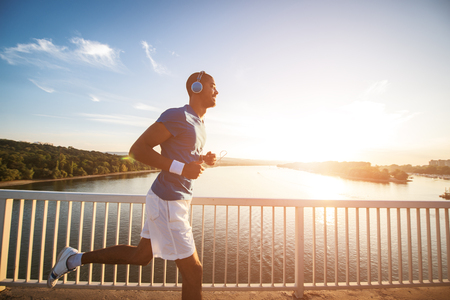 A young man running on the bridge along a river. Lens flare, warm tones.