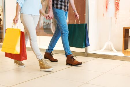 cuddling: Lower shot of a couple cuddling and carrying their shopping bags. Stock Photo