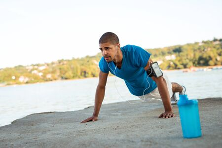ups: Young male athlete doing push ups next to the river.
