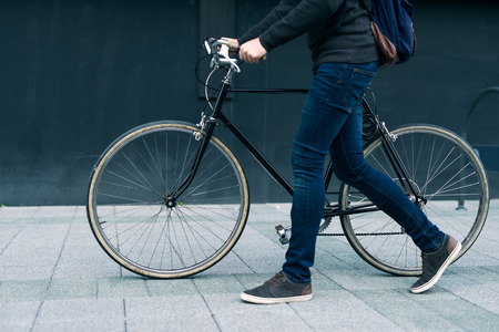 A young stylish businessman pushing a bicycle while going to work.