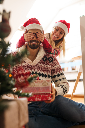 suprise: Cropped shot of a woman surprising her boyfriend with a Christmas gift. Stock Photo