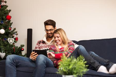 familia abrazo: Recortar foto de una pareja feliz en un estado de ánimo de Navidad que usa la tableta.
