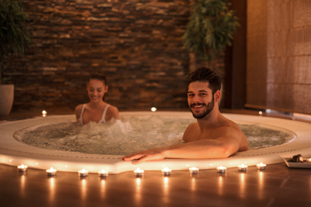 Portrait of an attractive young couple relaxing in a jacuzzi. High ISO image, ambiental light only. Banco de Imagens