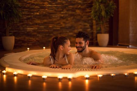 romântico: Retrato de um casal jovem e atraente relaxante em uma banheira de hidromassagem. Imagem de alta ISO, luz ambiental única.