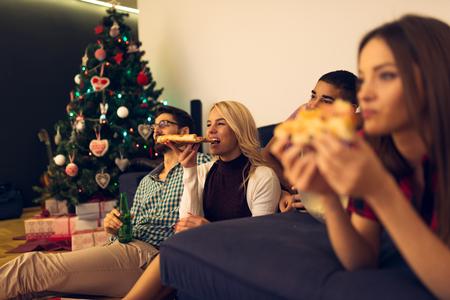 Shot von einem Freunde, die Pizza essen, trinken Bier und Fernsehen.