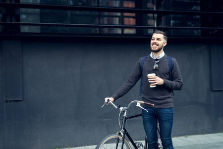 stylish men: Shot of a young smiling businessman going to work by bike. Stock Photo