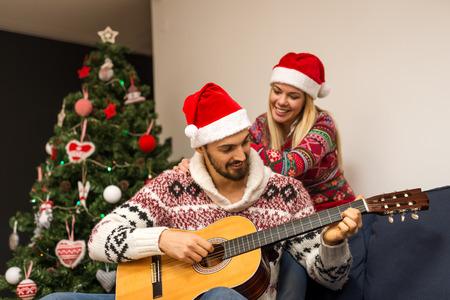 그의 여자 친구를위한 기타를 연주 남자의 샷입니다. 스톡 콘텐츠