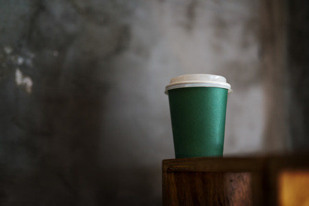 to go cup: Green coffee to go cup with no branding. Shallow dept of field