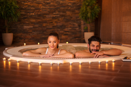hot guy: Portrait of an attractive young couple relaxing in a jakuzzi.