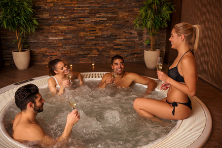 tubs: Shot of a friends enjoying in jacuzzi and drinking white wine.
