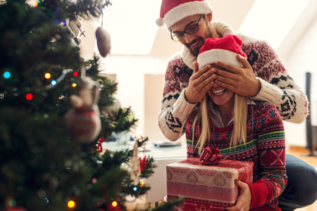 parejas jovenes: Recortar foto de un hombre asombrosamente su novia con un regalo de Navidad. Foto de archivo