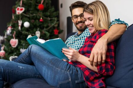 cuddled: Shot of a cuddled couple reading books. Selective focus.