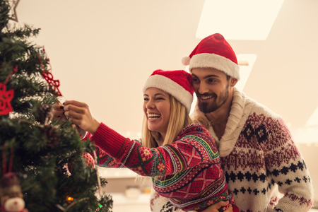 young tree: Shot of a young happy couple decorating a Christmas tree. Retro tonning. Stock Photo