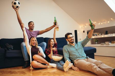 Foto van een groep van vrienden voetbal kijken en bier drinken.
