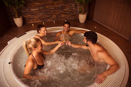 Shot of a group of friends drinking champagne and relaxing in jacuzzi.