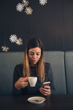 sip: Shot of a beautiful woman taking a sip of a coffee while using mobile phone.