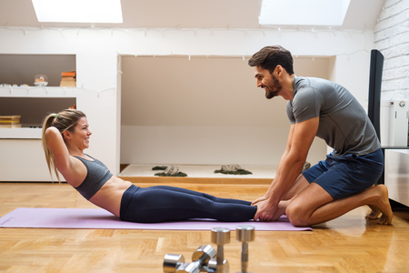 home trainer: Happy beautiful woman doing crunches with the assistance of her boyfriend. Stock Photo