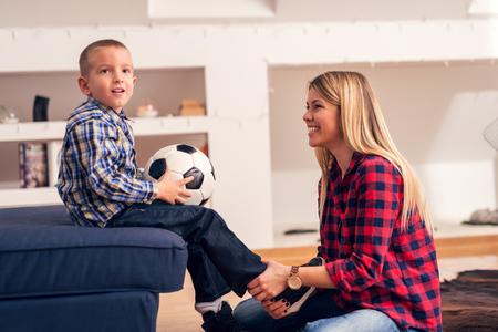 mamá hijo: Madre está poniendo en los zapatos en las piernas de los niños, preparándose para jugar al fútbol.