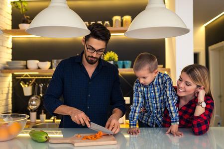 niños cocinando: Madre e hijo padre ayudando a preparar la cena familiar. Foto de archivo