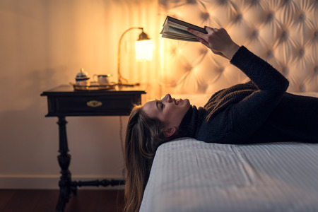 Attractive woman laying on the bed and reading a book.